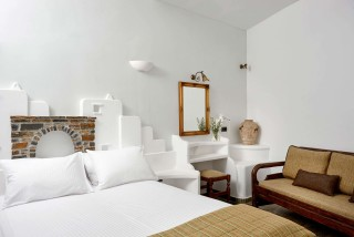 family suites porto klaras big bedroom with cycladic decoration, elegant furniture, sofa and minimal Cycladic decoration