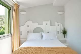 junior suite porto klaras bedroom with window that offers view of Kythnos island