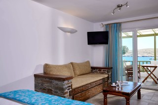superior studio porto klaras lounge area next to the bed with sea view and flat TV screen